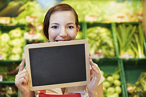 Germany, Cologne, Young woman with blackboard in supermarket, smiling, portrait - RKNF000009
