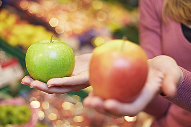 Germany, Cologne, Young woman comparing apples in supermarket - RKNF000024