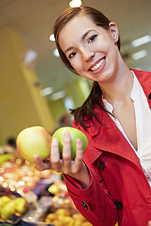 Germany, Cologne, Young woman comparing apples in supermarket - RKNF000027
