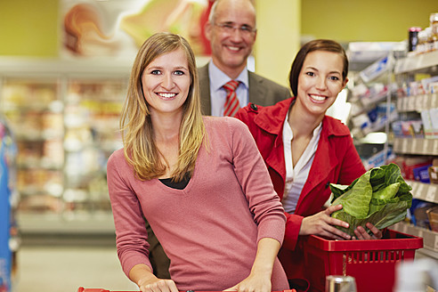 Germany, Cologne, Man and women in supermarket, smiling, portrait - RKNF000033
