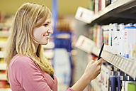 Germany, Cologne, Young woman with mobile in supermarket - RKNF000045