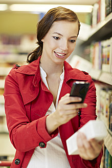 Germany, Cologne, Young woman with mobile in supermarket - RKNF000048