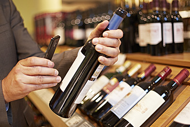 Germany, Cologne, Mature man taking picture of wine bottle in supermarket - RKNF000062