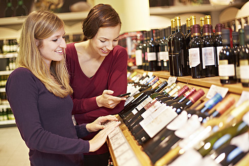 Germany, Cologne, Young women inspecting wine in supermarket - RKNF000065