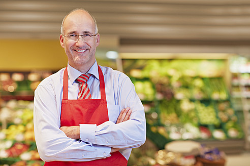 Germany, Cologne, Mature man in supermarket, smiling, portrait - RKNF000074