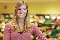 Germany, Cologne, Young woman in supermarket, smiling, portrait - RKNF000094