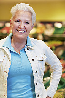 Germany, Cologne, Mature woman in supermarket, smiling, portrait - RKNF000097