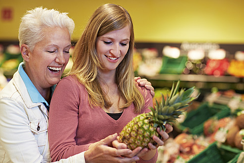 Germany, Cologne, Women with pineapple in supermarket - RKNF000100