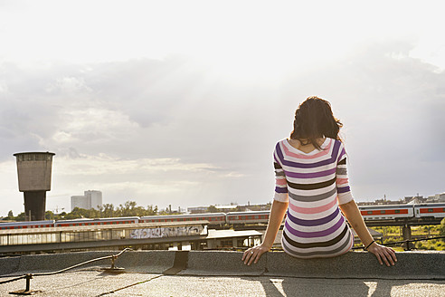 Germany, Hamburg, Young woman sitting at edge of roof - DBF000218