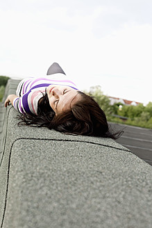 Germany, Hamburg, Young woman lying on wall - DBF000207