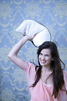 Germany, Munich, Young woman throwing pillow, smiling, portrait - KR000010
