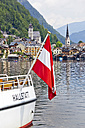 Austria, Upper Austria, Hallstatt, Boat with flag on lake, village in background - EJW000016