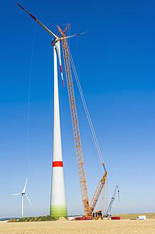 Germany, Saxony, Cnstruction of wind turbine with crane - MJ000076