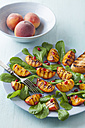 Peach salad garnished with pomegranate seeds and herb on plate - ECF000064