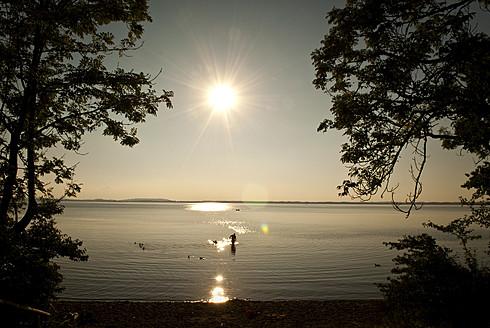 Germany, Bavaria, People bathing in Lake Chiemsee at sunset - KAF000016