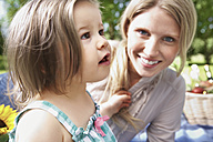 Germany, Cologne, Mother and daughter at picnic, smiling - PDYF000028