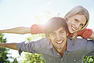 Germany, Cologne, Young couple flying, smiling, portrait - PDYF000034