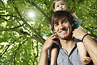 Germany, Cologne, Father carrying daughter on shoulders, smiling - PDYF000037
