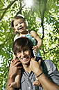 Germany, Cologne, Father carrying daughter on shoulders, smiling - PDYF000040