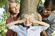 Germany, Cologne, Boy playing hide and seek with parents - PDYF000046