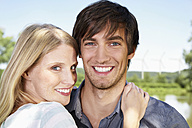Germany, Cologne, Young couple embracing, smiling, portrait - PDYF000058