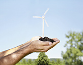 Germany, Cologne, Young man holding wind turbine with soil - PDYF000070