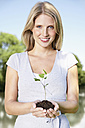 Germany, Cologne, Young woman holding seedling, smiling, portrait - PDYF000076