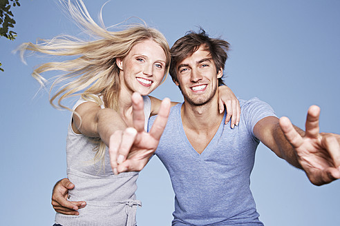 Germany, Cologne, Young couple showing peace sign, smiling, portrait - PDYF000082