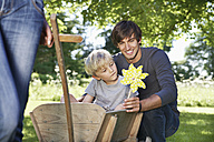 Germany, Cologne, Father and son with paper windmill, smiling - PDYF000106
