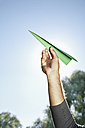 Germany, Cologne, Young man holding paper plane against sky - PDYF000112