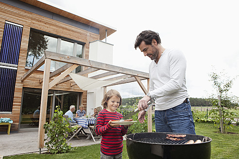 Germany, Bavaria, Nuremberg, Father and son preparing food on barbecue, family sitting in background - RBYF000121