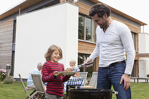 Germany, Bavaria, Nuremberg, Father and son preparing food on barbecue, family sitting in background - RBYF000124