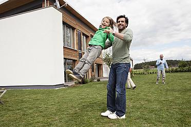 Germany, Bavaria, Nuremberg, Family playing in garden - RBYF000168