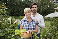 Germany, Bavaria, Nuremberg, Mature couple with vegetables in garden - RBYF000205