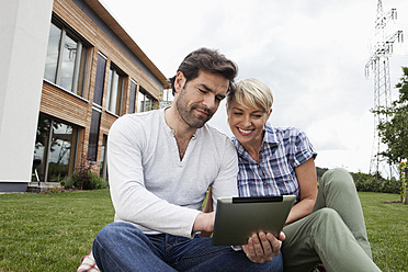 Germany, Bavaria, Nuremberg, Mature couple using digital tablet in garden - RBYF000208