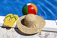 Austria, Linz, Beach ball floating on water, slippers and hat in foreground - EJWF000066