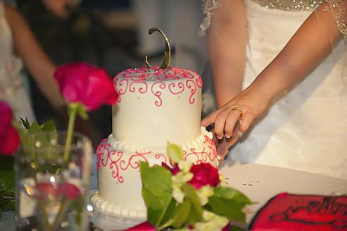 USA, Texas, Young bride cutting wedding cake - ABAF000240