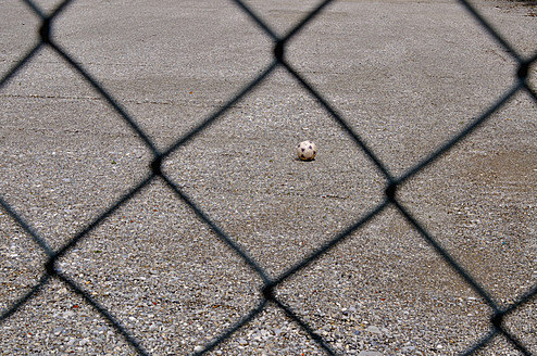 Germany, Bavaria, Football seen through wire mesh fence - AXF000212