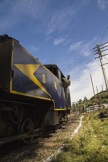 India, Tamil Nadu, Man on locomotive, Nilgiri Mountain Railway connecting Mettupalayam and Ooty - MBE000554