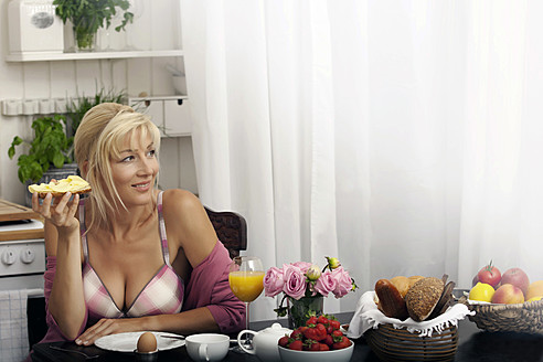 Germany, Munich, Mature woman having breakfast in kitchen - KRF000029