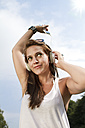 Germany, Berlin, Young woman listening music, close up - FKF000050