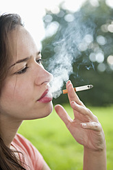 Germany, Berlin, Young woman smoking cigarette in park - BFRF000061