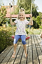 Germany, Bavaria, Girl swinging on swing, smiling, portrait - RNF001035