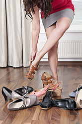 Germany, Berlin, Young woman trying on shoes - BFRF000068