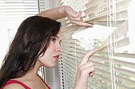 Germany, Berlin, Young woman looking through window blind, close up - BFRF000070