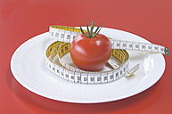 Red tomato on plate with measuring tape, close up - ASF004619