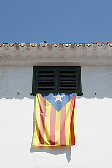 Spain, Menorca, Catalonia flag hanging out of window - JMF000214