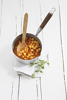 Potato chickpea soup in pot with wooden spoon on table - KSWF001010