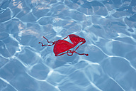 Germany, Red bikini top floating in swimming pool - JTF000010