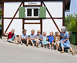 Germany, Bavaria, Woman sitting with group of children in front of small house - HSIYF000156